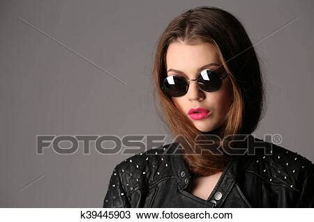 Lady in a studded leather jacket and circle sunglasses